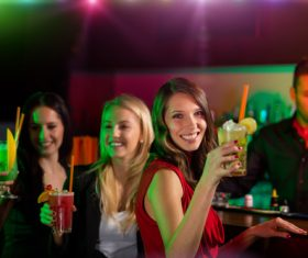 Woman drinking drink in front of nightclub bar Stock Photo
