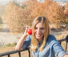 Woman holding heart shaped selfie using mobile phone Stock Photo 01