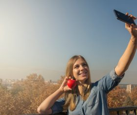 Woman holding heart shaped selfie using mobile phone Stock Photo 02