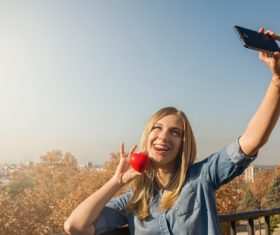 Woman holding heart shaped selfie using mobile phone Stock Photo 03