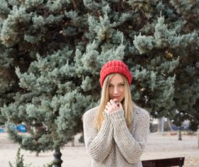 Woman in knit sweater standing in front of pine tree Stock Photo 01