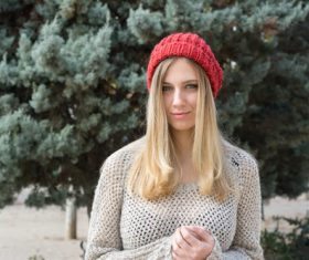 Woman in knit sweater standing in front of pine tree Stock Photo 02