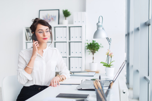 Woman making a call in the office Stock Photo