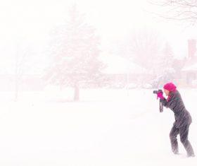 Woman shooting snow scene with camera Stock Photo