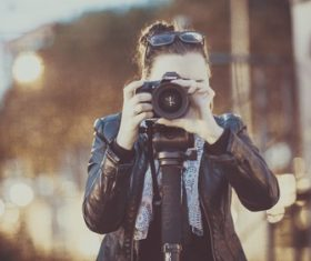 Woman shooting with camera Stock Photo