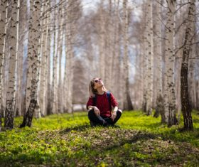 Woman sitting in birch forest Stock Photo