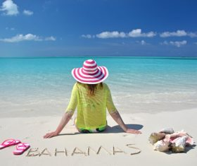 Woman sitting on the beach of Bahamas Stock Photo