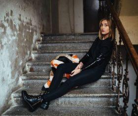 Woman sitting on the corridor ladder Stock Photo