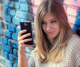 Woman sitting on the floor taking a selfie with a mobile phone Stock Photo