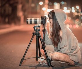 Woman sitting on the highway at night taking photos Stock Photo