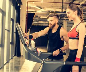 Woman standing on treadmill and coach adjusting treadmill Stock Photo