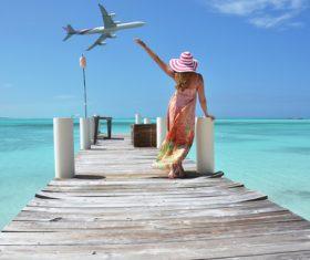 Woman standing on wooden bridge waving Stock Photo