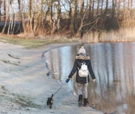 Woman walking the dog by the river Stock Photo