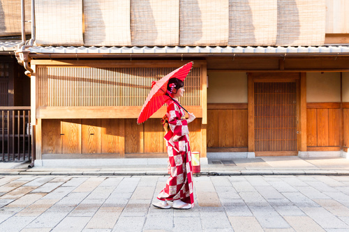 Woman wearing japanese national costume walking on the road Stock Photo