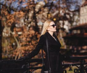 Woman wearing sunglasses standing on the bridge in autumn Stock Photo