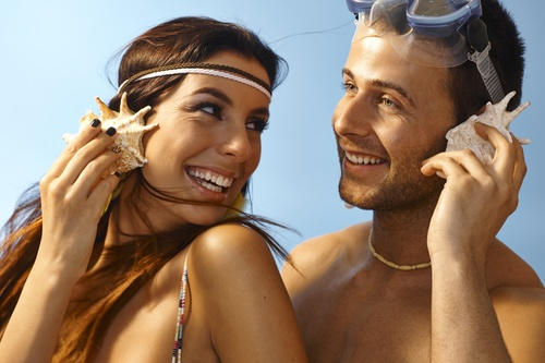 Young couple listening to conch Stock Photo