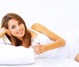 Young girl drinking water in bed Stock Photo 01