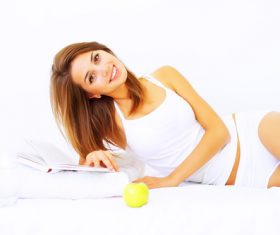 Young girl lying in bed reading book and putting an apple next to it Stock Photo