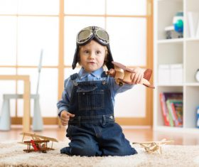 child playing with toy airplane at home Stock Photo 01