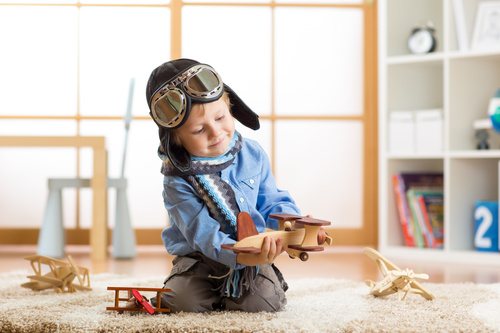 child playing with toy airplane at home Stock Photo 02