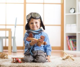child playing with toy airplane at home Stock Photo 03