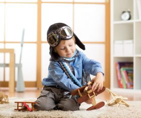 child playing with toy airplane at home Stock Photo 04