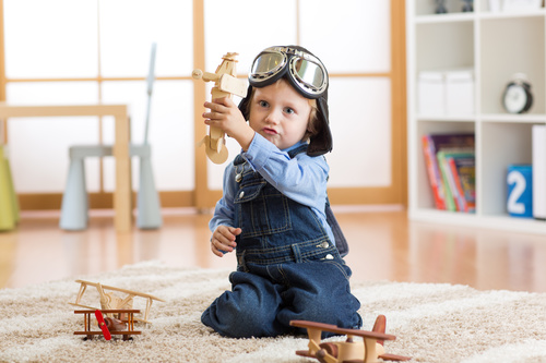 child playing with toy airplane at home Stock Photo 05