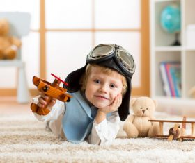 child playing with toy airplane at home Stock Photo 06