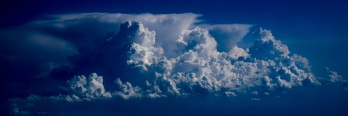 Airplane photographing cumulus clouds in the sky Stock Photo