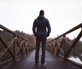 Back view of man standing on wooden bridge Stock Photo