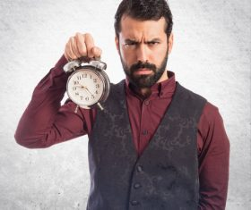 Bearded Man holding an alarm clock Stock Photo