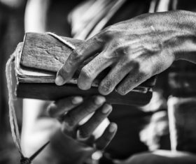 Black and white photo of hand holding bible Stock Photo