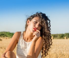 Carefree girl sitting in wheat field Stock Photo