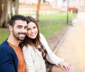 Couple sitting on a park bench Stock Photo