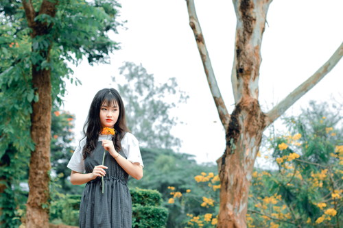 Girl holding a flower in hand Stock Photo