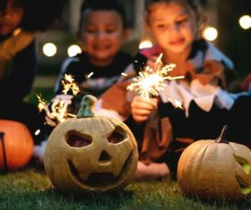 Halloween pumpkins and children putting fireworks Stock Photo