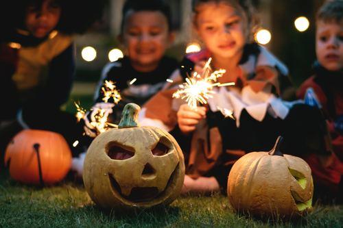 Halloween pumpkins and children putting fireworks Stock Photo