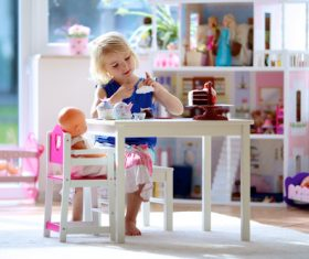 Little girl playing mini doll house at home Stock Photo 01