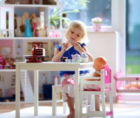 Little girl playing mini doll house at home Stock Photo 02