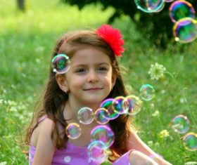 Little girl sitting on the grass looking at soap bubbles Stock Photo
