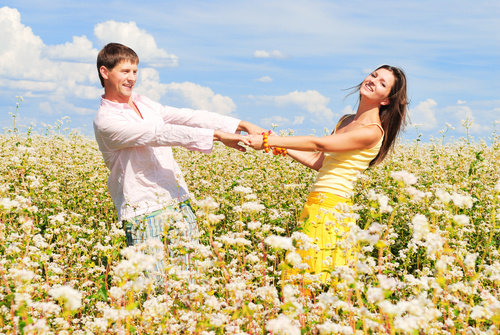 Lovers hand in hand in the flowers Stock Photo