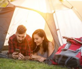 Lovers listening to music on the phone in camping tent Stock Photo