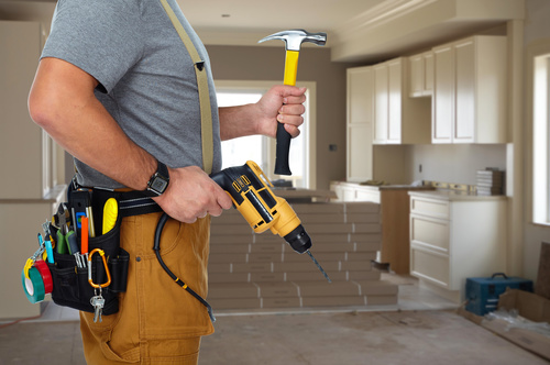Maintenance worker holding hammer and electric drill Stock Photo