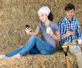 Male and female holding a glass of milk and playing with mobile phones Stock Photo