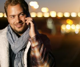 Man answering the phone and blurred lights behind him Stock Photo