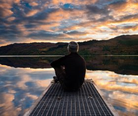 Man sitting by lake Stock Photo