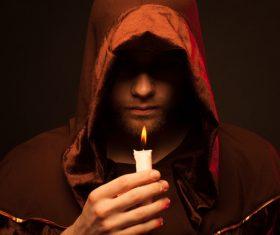 Man wearing cloak holding candle Stock Photo