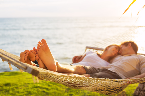 Men and women lying together in hammock Stock Photo