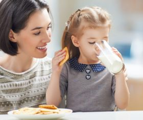 Mother looking at daughter eating breakfast Stock Photo