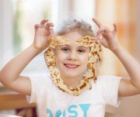 Naughty little girl holding pancake Stock Photo
